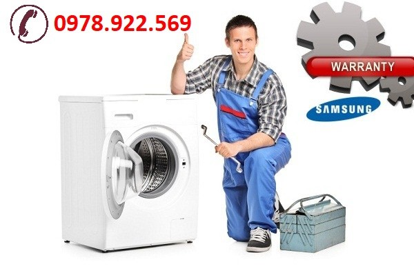 A repairman holding a spanner and giving thumb up next to a washing machine isolated on white background